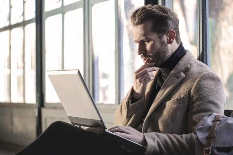 man sitting with laptop, pondering