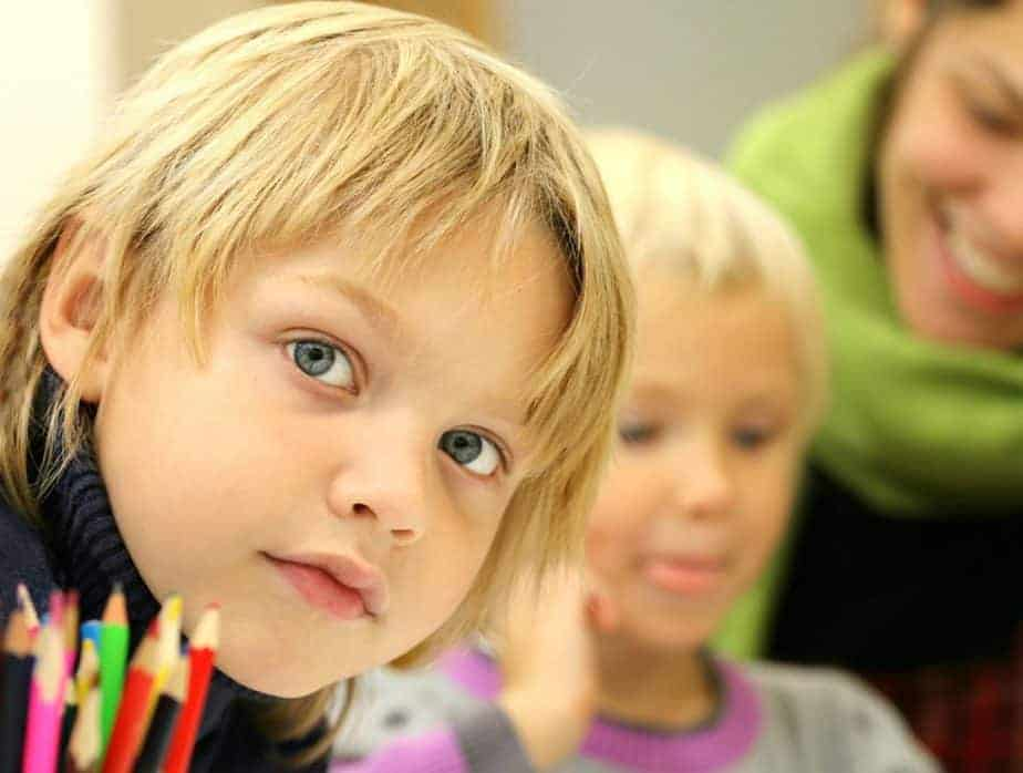 Young student looking into the camera while working in the classroom