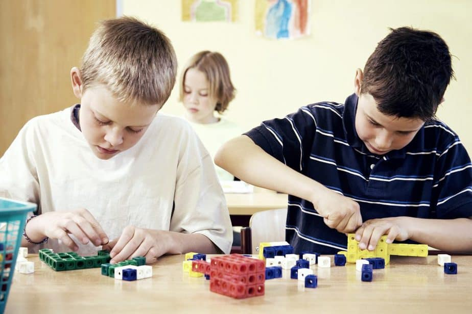 Children assembling plastic blocks in the classroom, learning life skills to help aid in student success