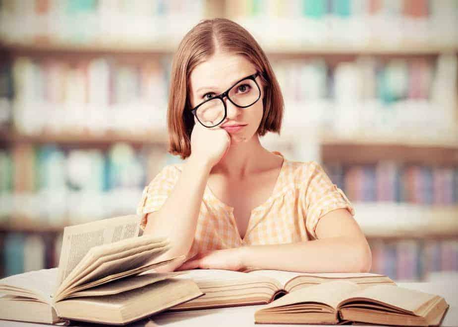 tired female teacher with glasses reading books, overwhelmed