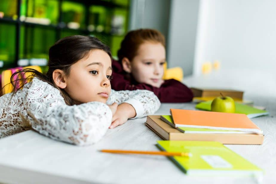 Two young girls with chins on their desks, looking bored