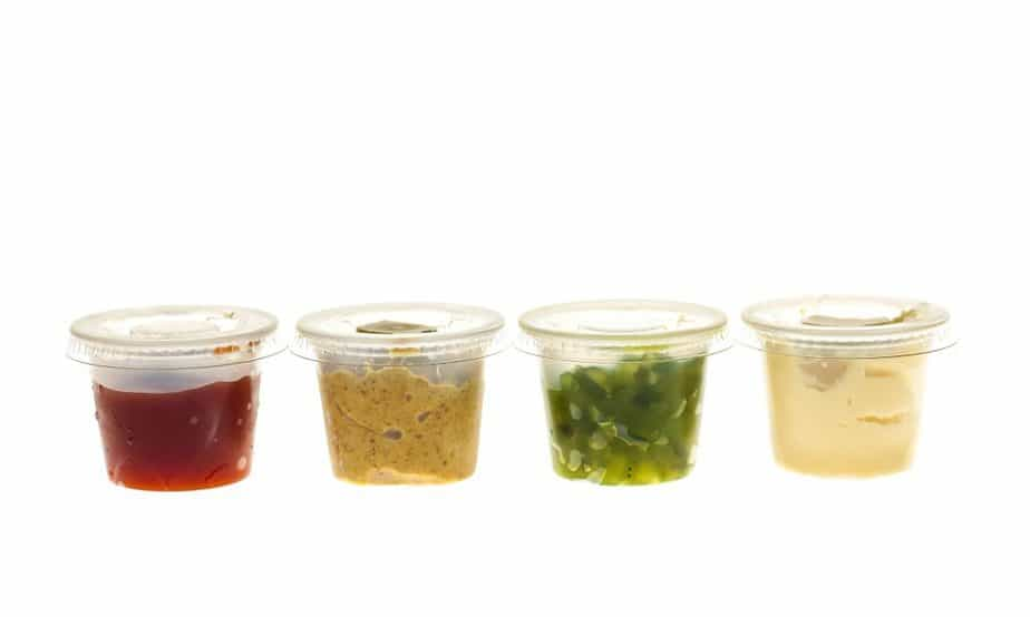 Relish mustard ketchup and mayonnaise condiments in clear containers on white background