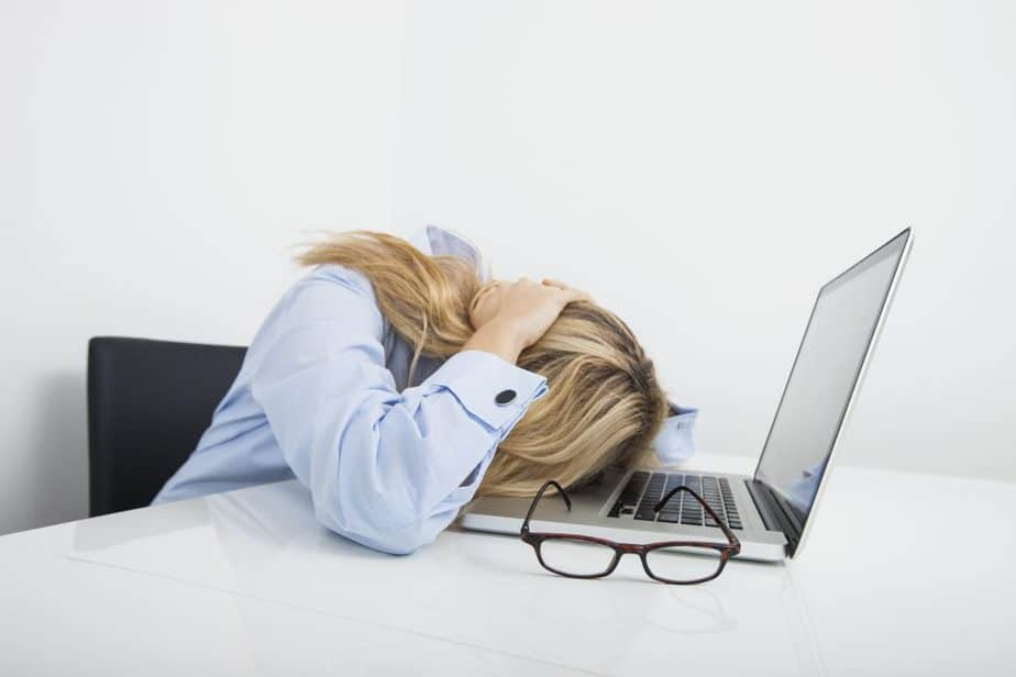 Tired female resting head on laptop at desk
