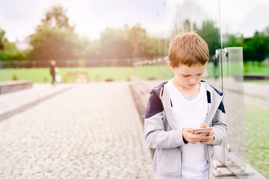 Little boy child playing mobile games on smartphone in the park.